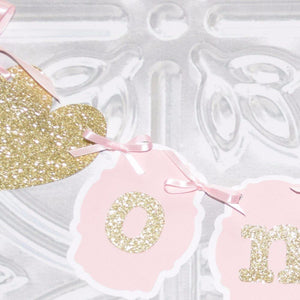 gold sparkle and pink details of a first birthday banner