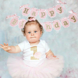 Little girl celebrating first birthday in pink tutu with a pink and gold happy birthday banner