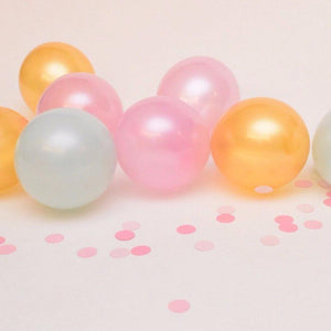 pink, gold and mint balloons surrounded by pink confetti