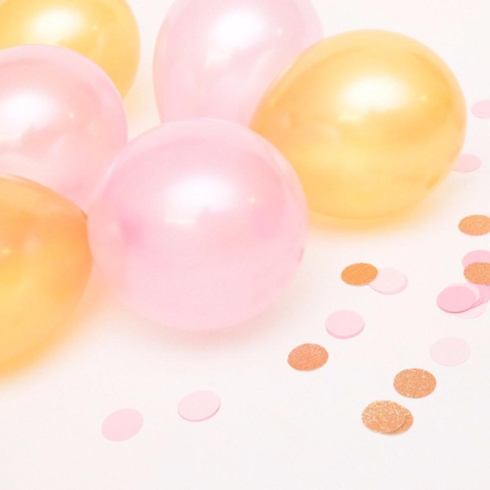 pink and gold balloons surrounded by pink and gold confetti