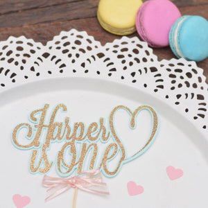 Harper is One with heart cake topper with gold sparkle and aqua details on white cake with colourful macaroons