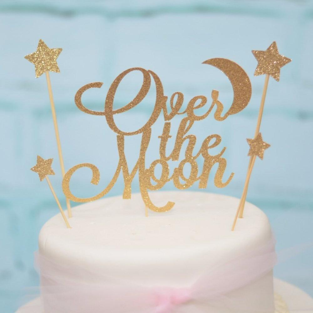 Over the moon cake topper with star and moon details in sparkly gold glitter