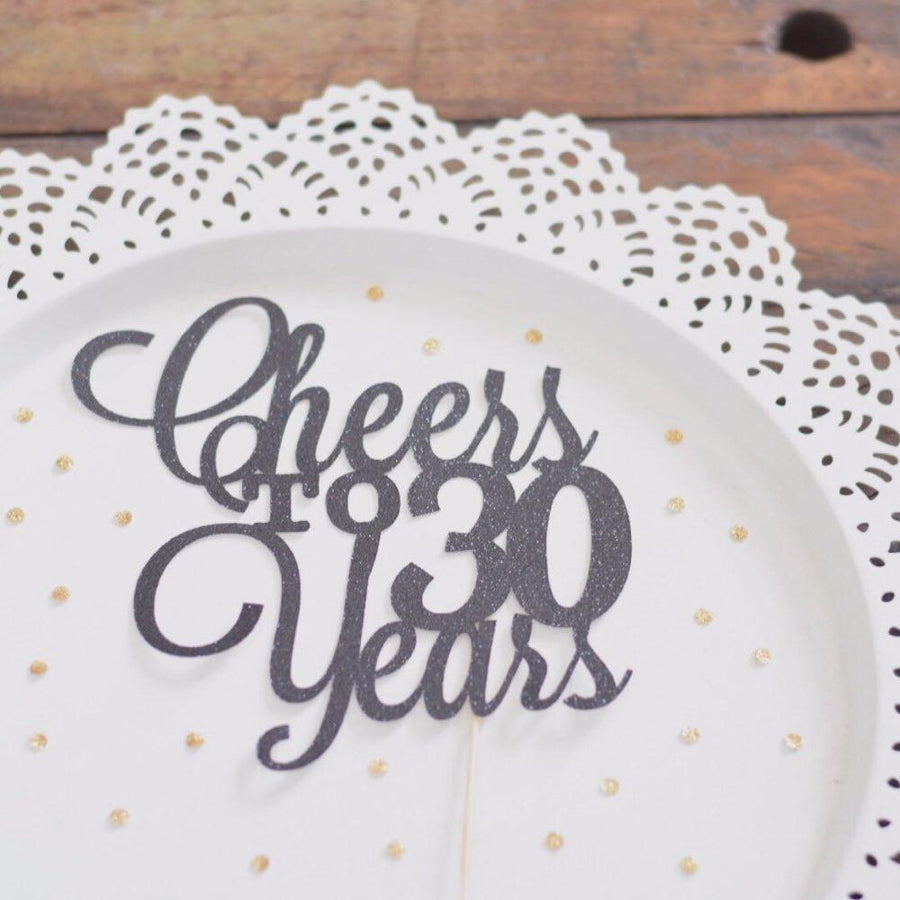 Cheers to 50 years black glitter cake topper on white plate background with black feathers