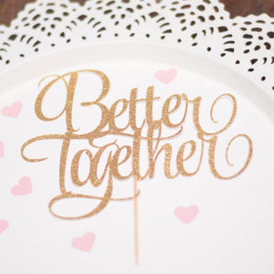 Better Together gold glitter cake topper on stick with white plate and pink hears