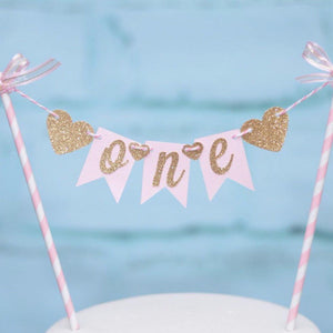 One gold and pink cake topper with gold sparkle hearts and pink and white straws