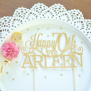 Happy 70th Arleen gold glitter cake topper on white plate with pink flowers