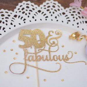 50 & fabulous gold glitter cake topper on white plate