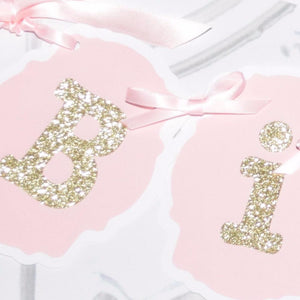 B and i gold sparkle banner letters on pink background