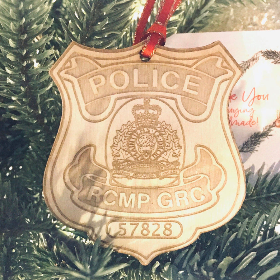 RCMP badge laser cut onto wood with a red and gold ribbon hanging on a tree