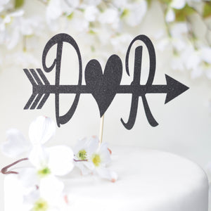 D heart R initials on an arrow on a white cake with white flowers