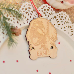 Leonberger dog ornament on a white with greenery and confetti