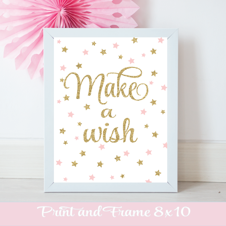 Pink and gold Make a Wish Sign with sparkly framed in a white frame with a pink pinwheel on the wall