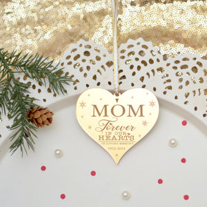 Memorial ornament for Mom on a white plate with Christmas greenery