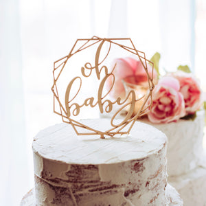 oh baby geometric cake topper on a naked cake for a baby shower