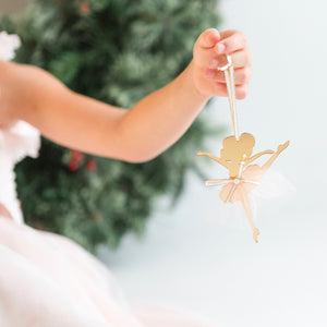 Little hand holding up a gold and white ballerina Christmas ornament