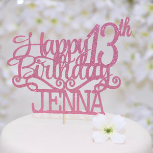 Happy 13th Birthday Jenna pink cake topper on a white cake with white flowers