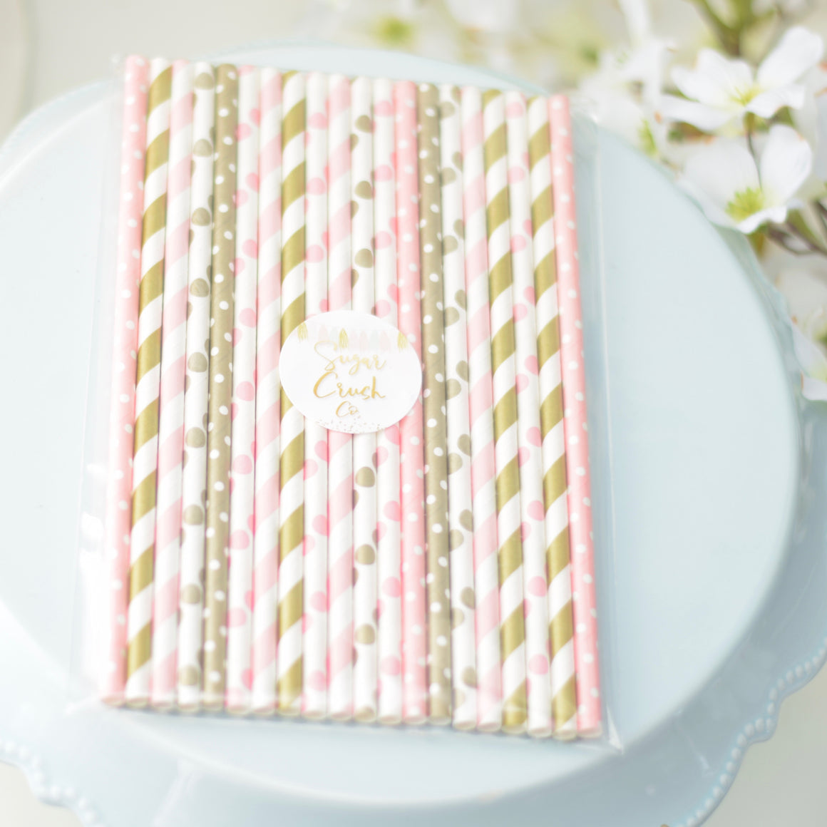 pink and gold straws on a cake stand