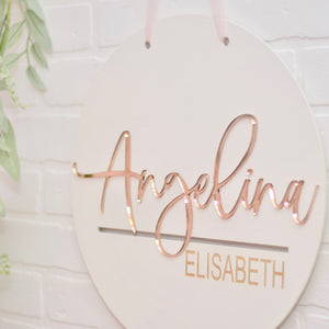 rose gold name sign on white brick wall