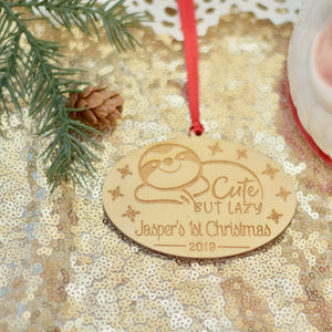 Sloth ornament for sloth lover with Jasper's 1st Christmas lying on a gold sparkly sequin cloth