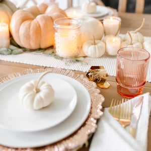 Pumpkins, candles, white plates and gold place cards
