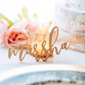 marsha place card laser cut wood name leaning against a candle with flowers on table