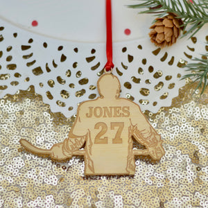hockey jersey ornament made out of wood placed on gold sparkly table cloth