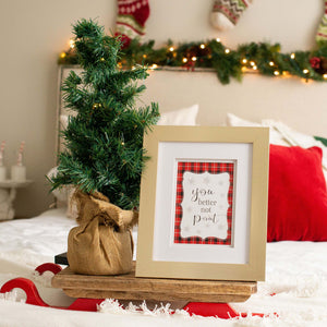 Gold framed christmas sign on bed with christmas tree