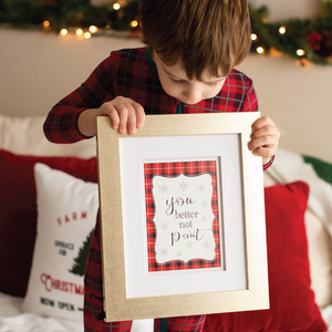 Boy in Christmas PJs holding a sign You better not pout Christmas photography