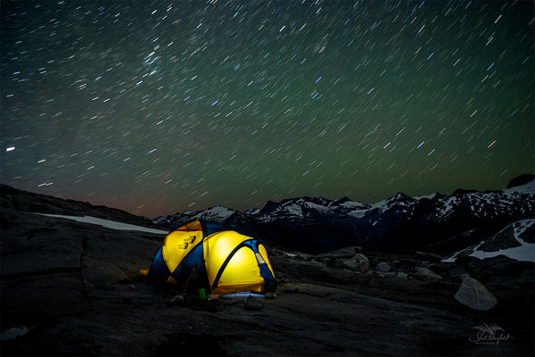 Starry night sky over yellow north face tent with mountains in the background. Photography by Shel Neufeld from Roberts Creek, BC, Canada.