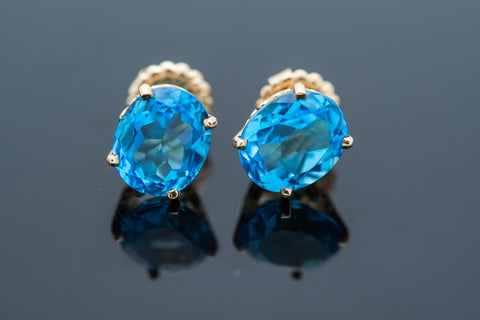 Beautiful large oval Blue Topaz Earrings set in ornate 14 karat yellow gold settings