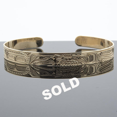 The Wolf and the Eagle captured beautifully in 14 karat yellow gold in this elegant cuff bracelet