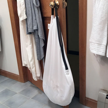 white bum genius hangout wet bag in a bathroom diaper storage