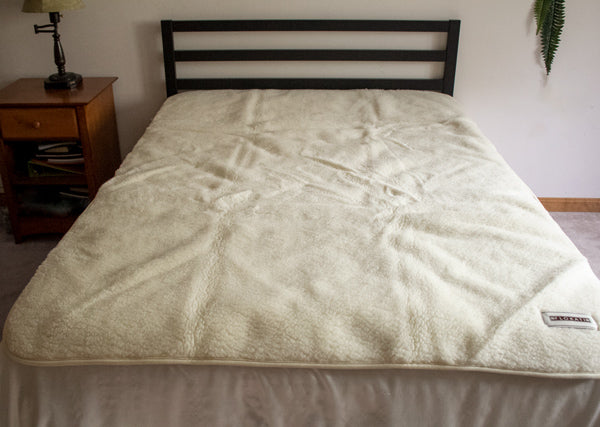 Flokati merino wool bed pad on a full size bed