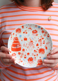 Holding Illustrated Plate Featuring Cake & Cupcakes