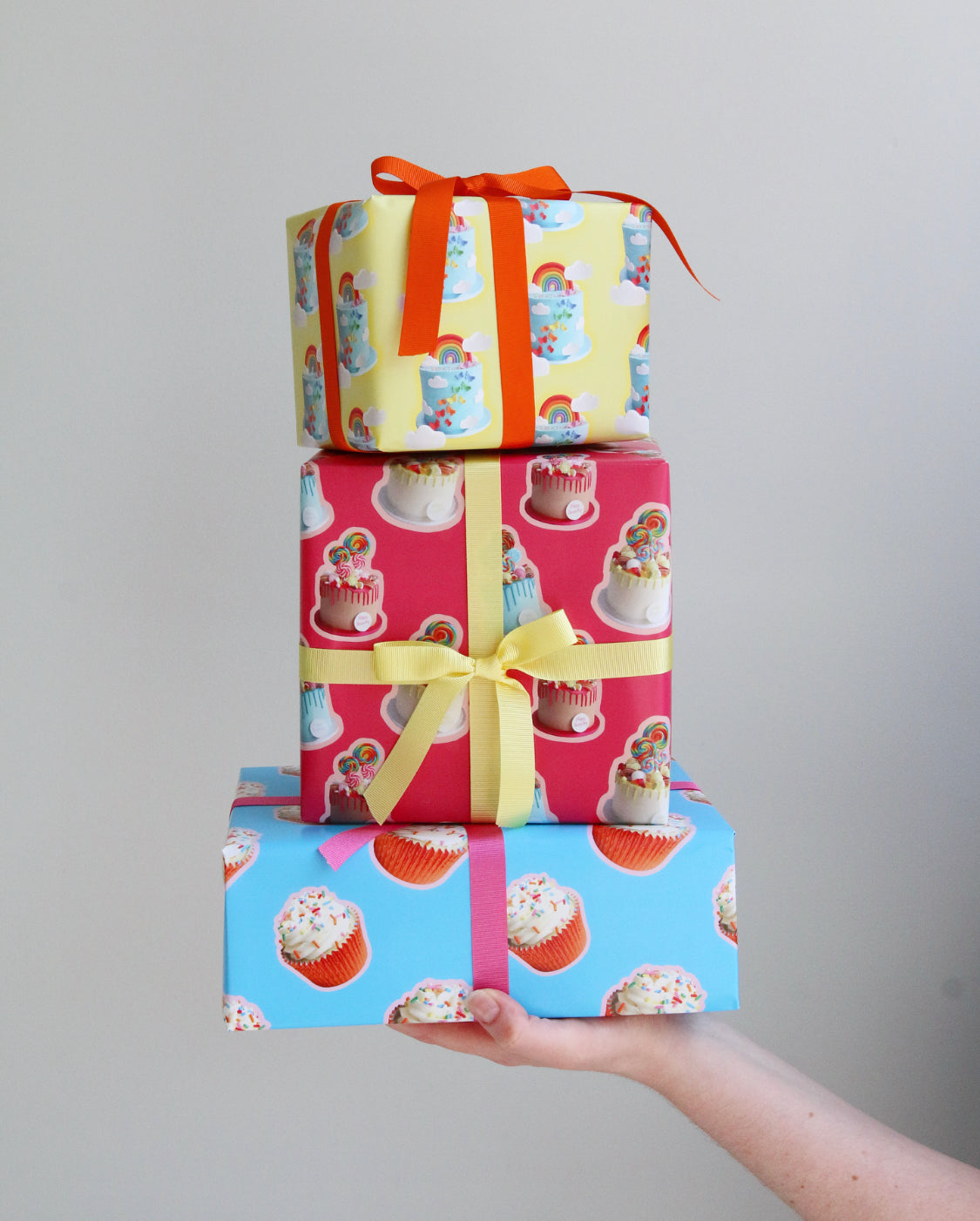 Stack of three presents wrapped with cake wrapping paper