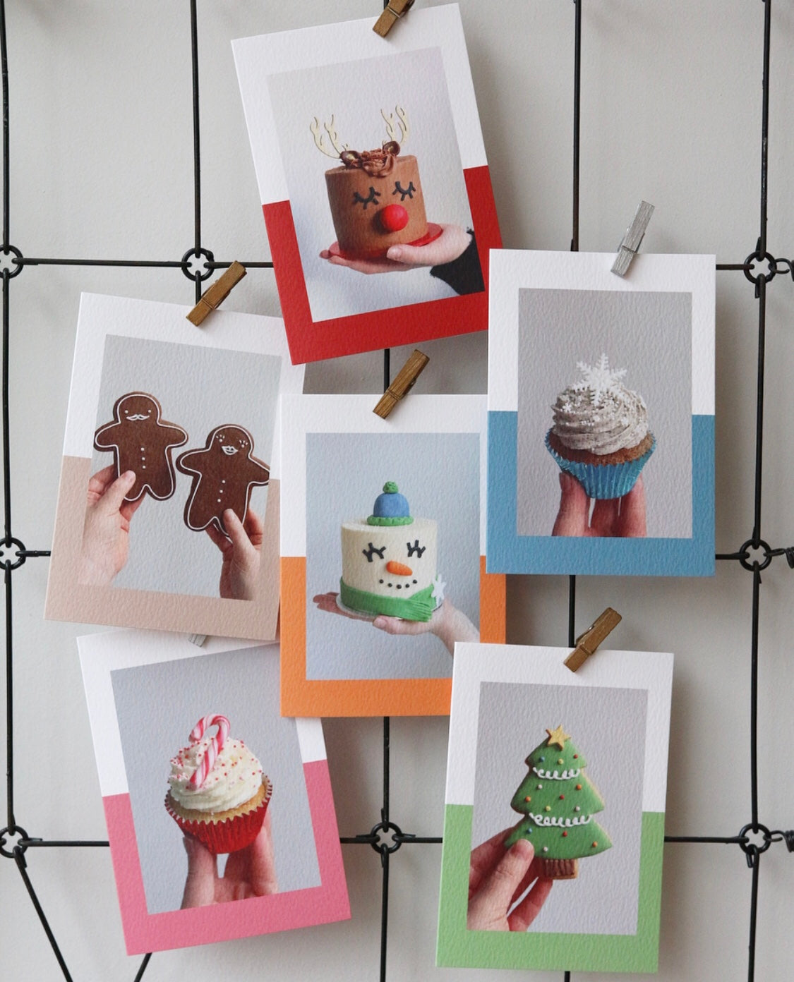 Selection of Christmas Cards with Photos of Cakes, Cupcakes and Biscuits Hanging on Wall
