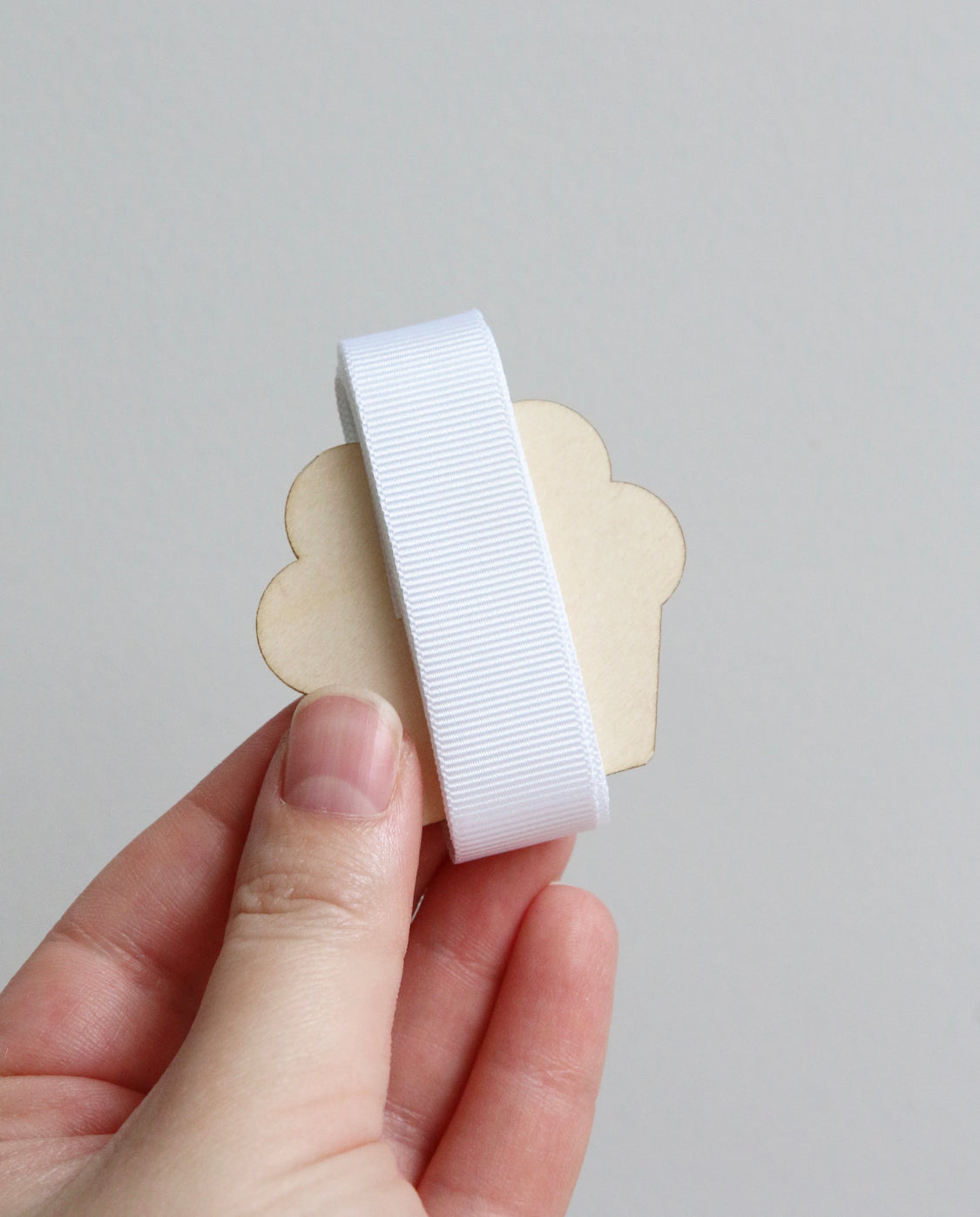 White grosgrain ribbon on wooden cutout cupcake
