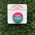 She/They button (pink/teal)