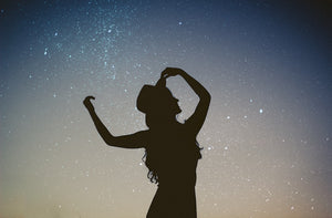 silhouette of woman against a starry sky