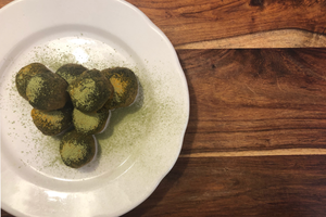 Matcha bliss balls on white plate and wood board