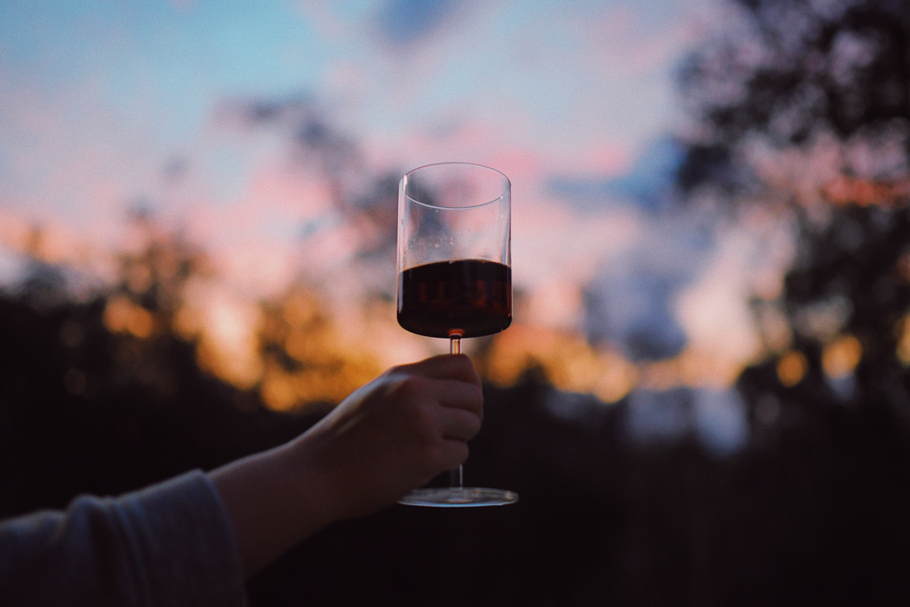 person holding glass of wine at sunset
