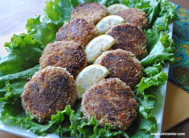 Zaatar crab cake plated on bed of lettuce with lemon wedges