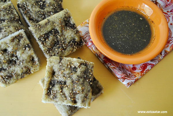 Zaatar Focaccia Bread cut into squares with zaatar olive oil dip mixture