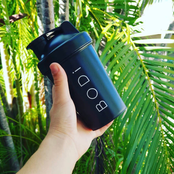 hand holding a matte black BODi protein shaker for meal replacements