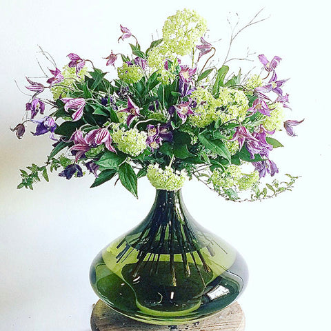 green vase with lilac clematis and green guelder roses