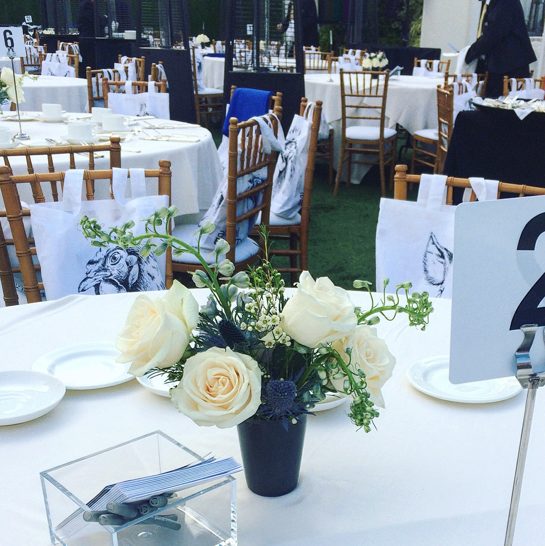 small table centerpiece with white roses, blue delphinium and thistles for an Animal Equality event