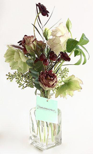 A selection of seasonal flowers in a glass bottle.