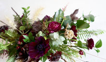 An arrangement bursting with seasonal flowers and foliages in shades of green and burgundy and is designed in a low and horizontal style.