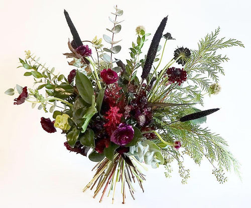 A bouquet bursting with seasonal flowers and foliage in green and burgundy shades with lots of seasonal foliage and texture.