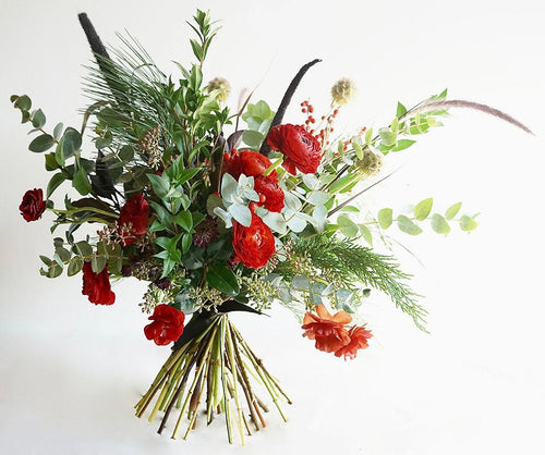 A bouquet bursting with seasonal flowers and foliage in the traditional green and red colors of Christmas.